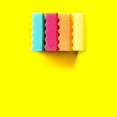 Colored dishwashing sponges orange, red, blue, yellow on yellow background Standard-Bild - 121337595