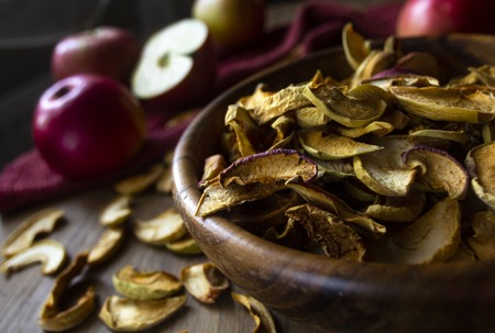 Homemade dried apples in a bowl and fresh ripe apples on wooden table Standard-Bild - 123431221