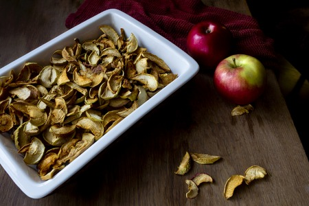 Homemade dried apples in a dish and fresh ripe apples on wooden table Standard-Bild - 123431223