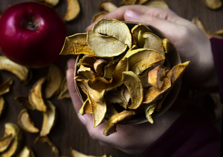 Female hands with homemade dried apples in a bowl, wooden table on the background Standard-Bild - 123431227