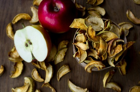 Homemade dried apples and fresh ripe apples on wooden table, top view. Standard-Bild - 123431229