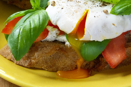 Healthy breakfast sandwiches with poached egg, tomato and basil Standard-Bild - 123431240