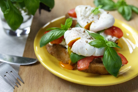 Healthy breakfast sandwiches with basil, tomato and poached egg Standard-Bild - 123431274