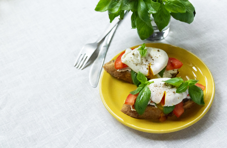 Healthy breakfast sandwiches with basil, tomato and poached egg. copy space Standard-Bild - 123431281