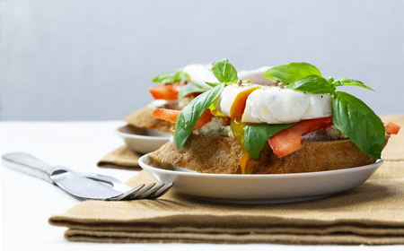Healthy breakfast sandwiches with poached egg, tomato and basil Standard-Bild - 123431282