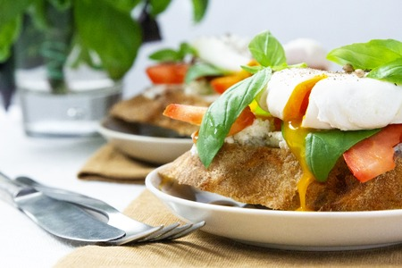 Healthy breakfast sandwiches with basil, tomato and poached egg Standard-Bild - 123431284