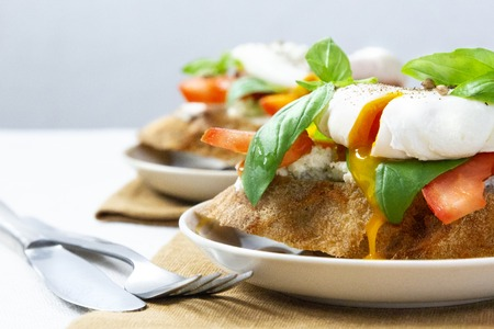 Healthy breakfast sandwiches with poached egg, tomato and basil Standard-Bild - 123431285