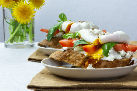 Healthy breakfast sandwiches with basil, tomato and poached egg Standard-Bild - 123431286