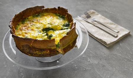 Homemade pie Quiche lorraine with salmon, cheese and spinach served on a glass stand Standard-Bild - 123431290