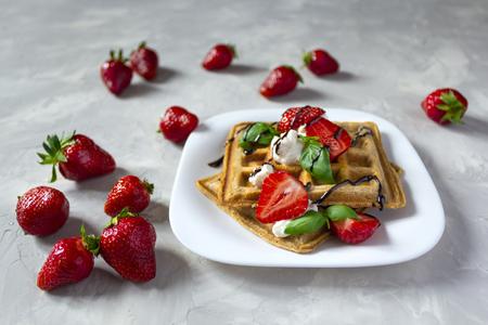 Belgium waffles dessert with strawberries, basil, ricotta cheese and chocolate. Standard-Bild - 126843693