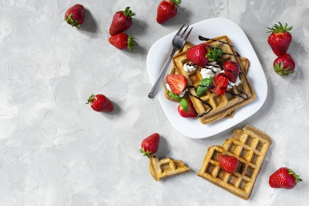 Belgium waffles with strawberries, ricotta cheese and chocolate on white plate. Top view. Copy space Standard-Bild - 126843706
