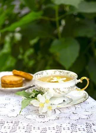 Jasmine herbal tea in a porcelain Cup with biscuit on lace table cloth Standard-Bild - 126843716