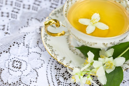 Jasmine tea in a porcelain Cup and jasmine flowers on lace table cloth, top view Standard-Bild - 126843718