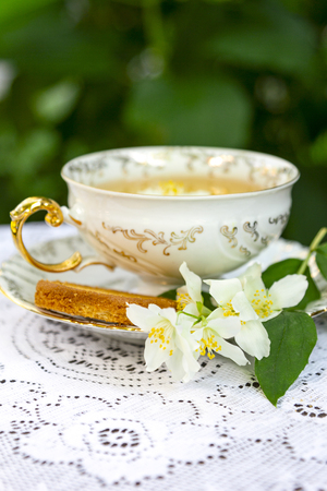 Jasmine herbal tea in a porcelain Cup with biscuit on lace table cloth Standard-Bild - 126843719