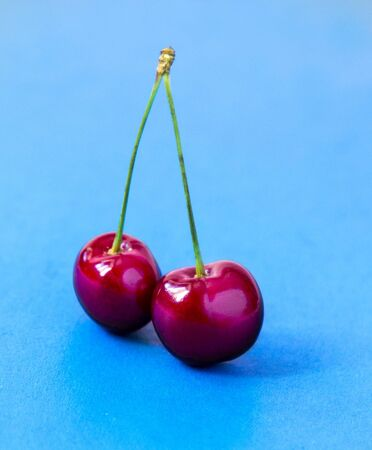 Two raw Red Cherries on a blue background Standard-Bild - 126843735