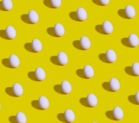 Pattern of white eggs on a pastel yellow background. Easter template