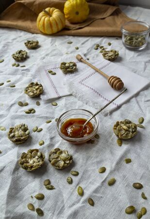 Organic candy made with pumpkin seeds. Fitness Cookies on a linen tablecloth. monochrome colors 版權商用圖片