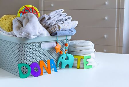 Donation box with Baby Unisex neutral clothing and donation accessories on light background