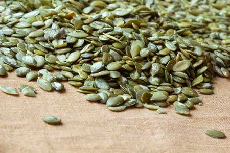 close-up of Pumpkin seeds on the linen background. Monochrome colors