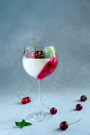 Individual dessert in wine glass with cherry. Panna cotta with berries in glass on grey background.