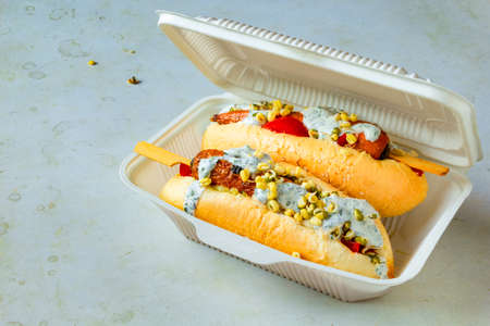 Hot dog with carrots. Disposable tableware with vegetarian fast food