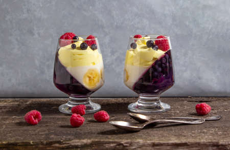 glass jars with dessert (panna cotta, jelly, mousse, pudding) with bilberry and banana layers on wooden rustic table