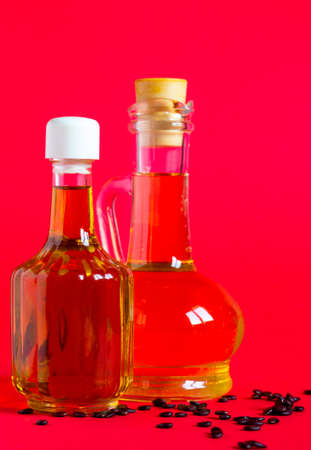 Watermelon seed oil in a glass jars on red background