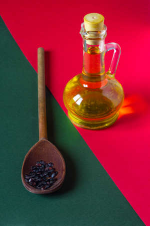 Watermelon seed oil in a glass jar and raw seeds in a spoon on red and green background Archivio Fotografico