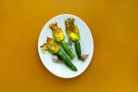 Fried Zucchini Flowers Stuffed with cream cheese with garlic on white plate on the honey mustard color background Archivio Fotografico