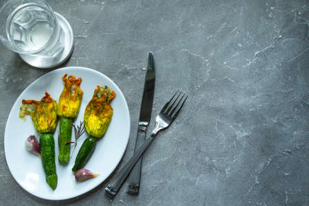 Fried Zucchini Flowers Stuffed with cream cheese with garlic on white plate. Copy space