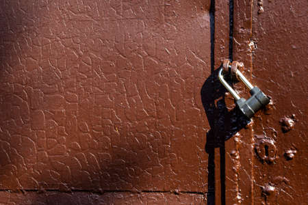 Fragment of an old brown metal gate with a lock, texture with cracks on old paint Archivio Fotografico