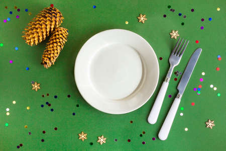 Top view of festive Christmas table setting on green background with confetti