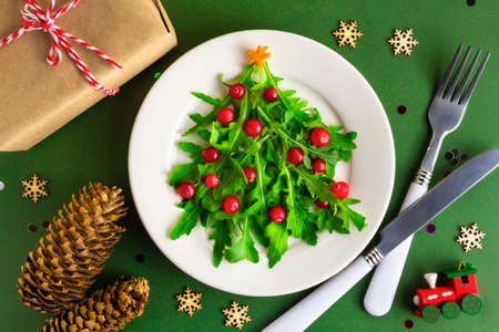 The Christmas tree salad on white plate on table. Flat lay
