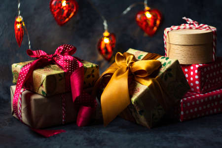 Christmas presents in red and natural colored paper on a dark background Archivio Fotografico