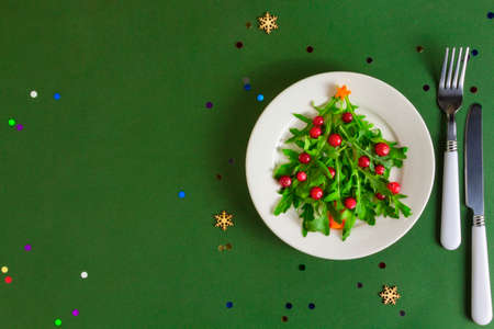 The Christmas tree salad on white plate on green background with copy space. Flat lay