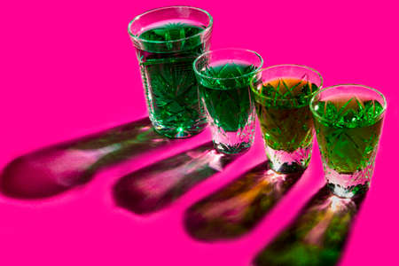 Strong alcohol. shot glasses with absinthe on pink background