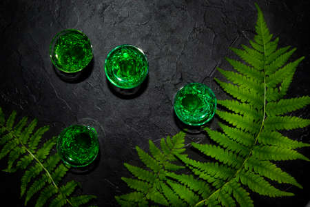 Strong alcohol. shot glasses with absinthe. Dark stone background