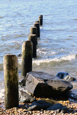 pilings: Old Pilings By Rock On Shoreline Stock Photo