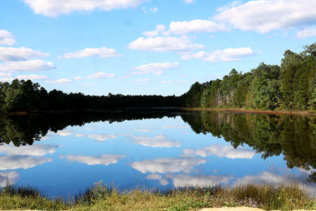 Blue sky, clouds, and trees are reflected in the rippling water. Stock Photo