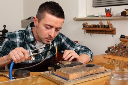Goldsmith in workshop. Making of jewelery. Handmade.  Standard-Bild