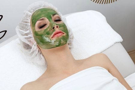 Closeup of beautiful woman, resting with clay mask on her face.