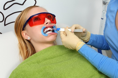 Teeth whitening. Pro at work with her pacient.