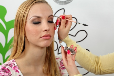 Professional makeup artist applying mascara on the eyebrows of a beautiful girl.  photo