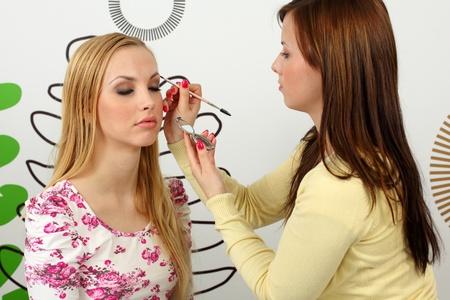 Professional makeup artist applying mascara on the eyebrows of a beautiful girl.