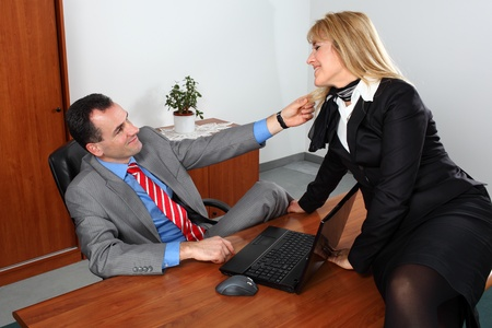 Businessman and businesswoman flirting in the office.  photo
