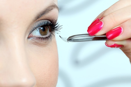 beauty woman: Insertion of false eyelashes. Close up. Stock Photo