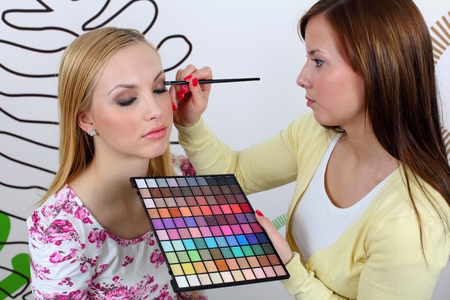 Professional makeup artist applying makeup to attractive young woman face.  photo