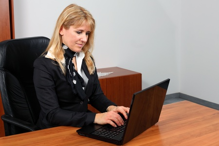 Attractive secretary is typing and sending e-mail.  Standard-Bild