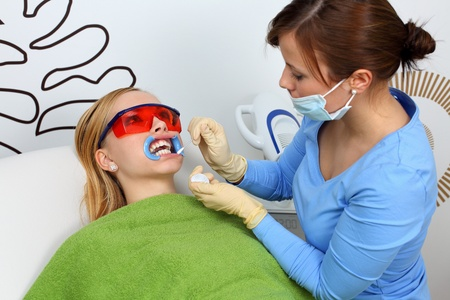 surgical glove: Teeth whitening. Pro at work with her pacient.