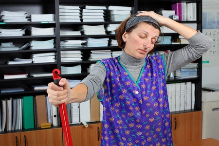 Tired professional cleaning lady at her work in the office  photo